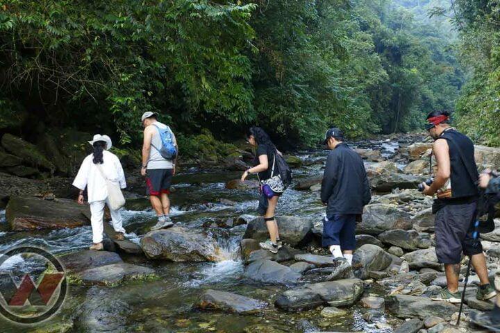 guía indígena cruzando rio con turistas